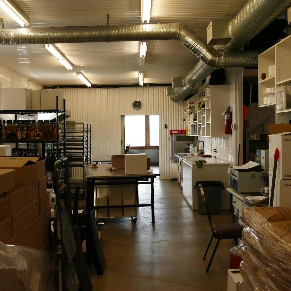 Un atelier de trasformation alimentaire avec des empilements de sacs et de cartons, et des étagères.