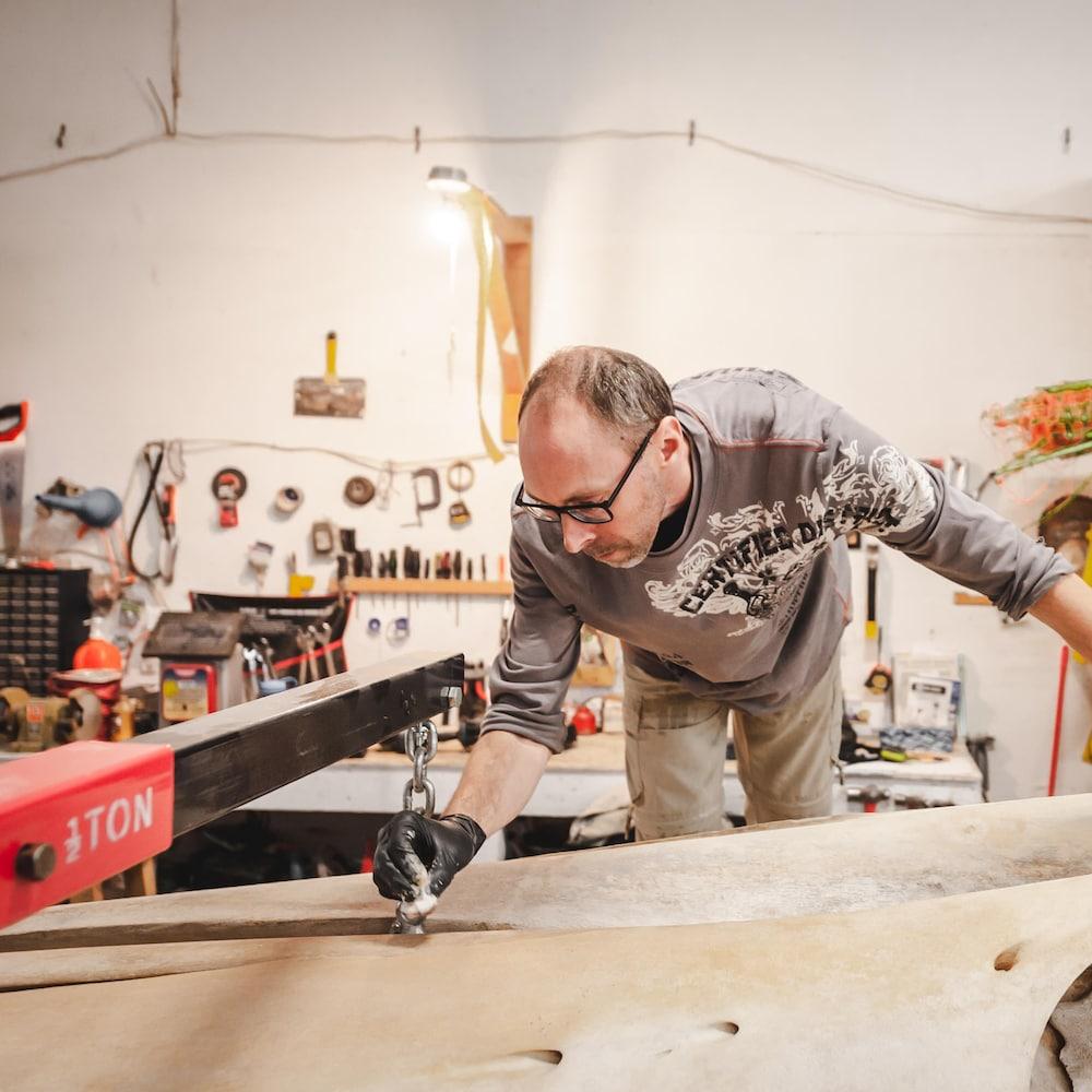 Un des travailleurs du GREMM essuie la surface d'un squelette de baleine.