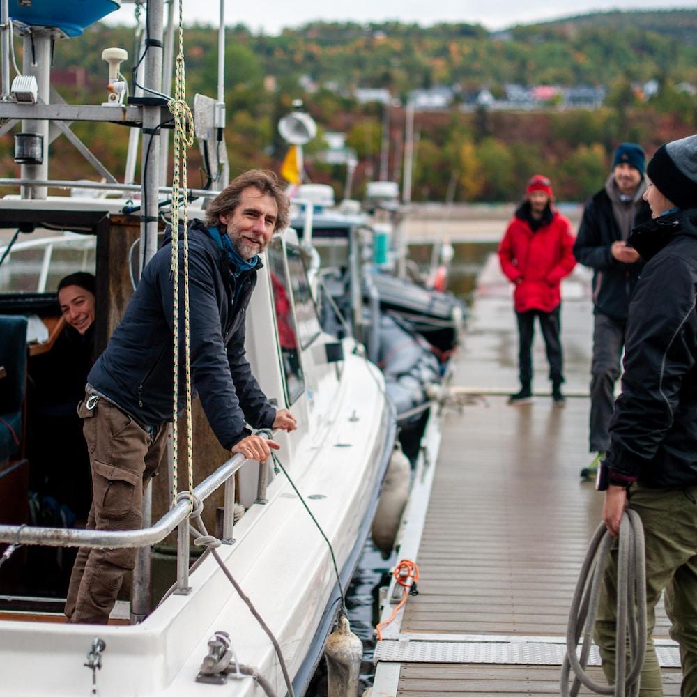 Le capitaine est appuyé sur la bordure du bateau et discute avec des gens qui sont sur le quai de la marina.