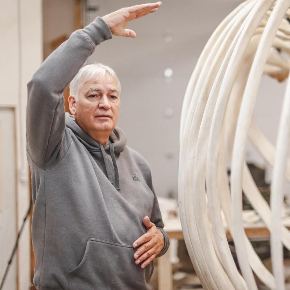 Patrice Gobeil donne des indications, aux côtés d'un squelette de baleine.