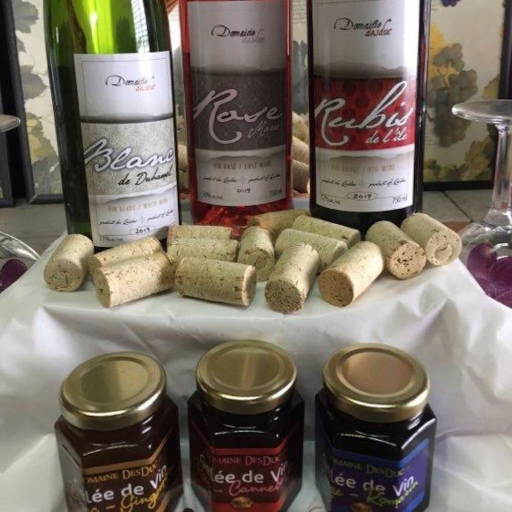 Trois bouteilles de vin et trois petits pots de gelées posées sur une table avec une nappe blanche.