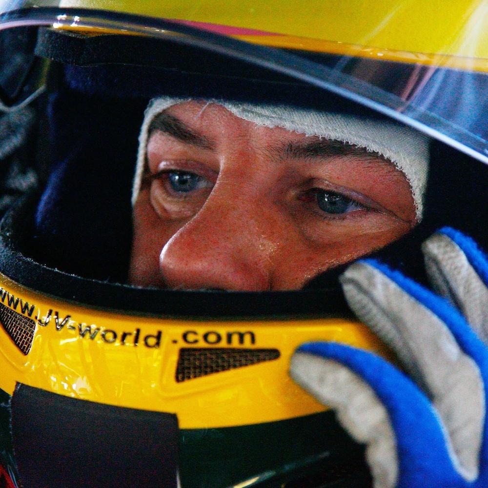 Jacques Villeneuve porte un casque de pilote automobile.