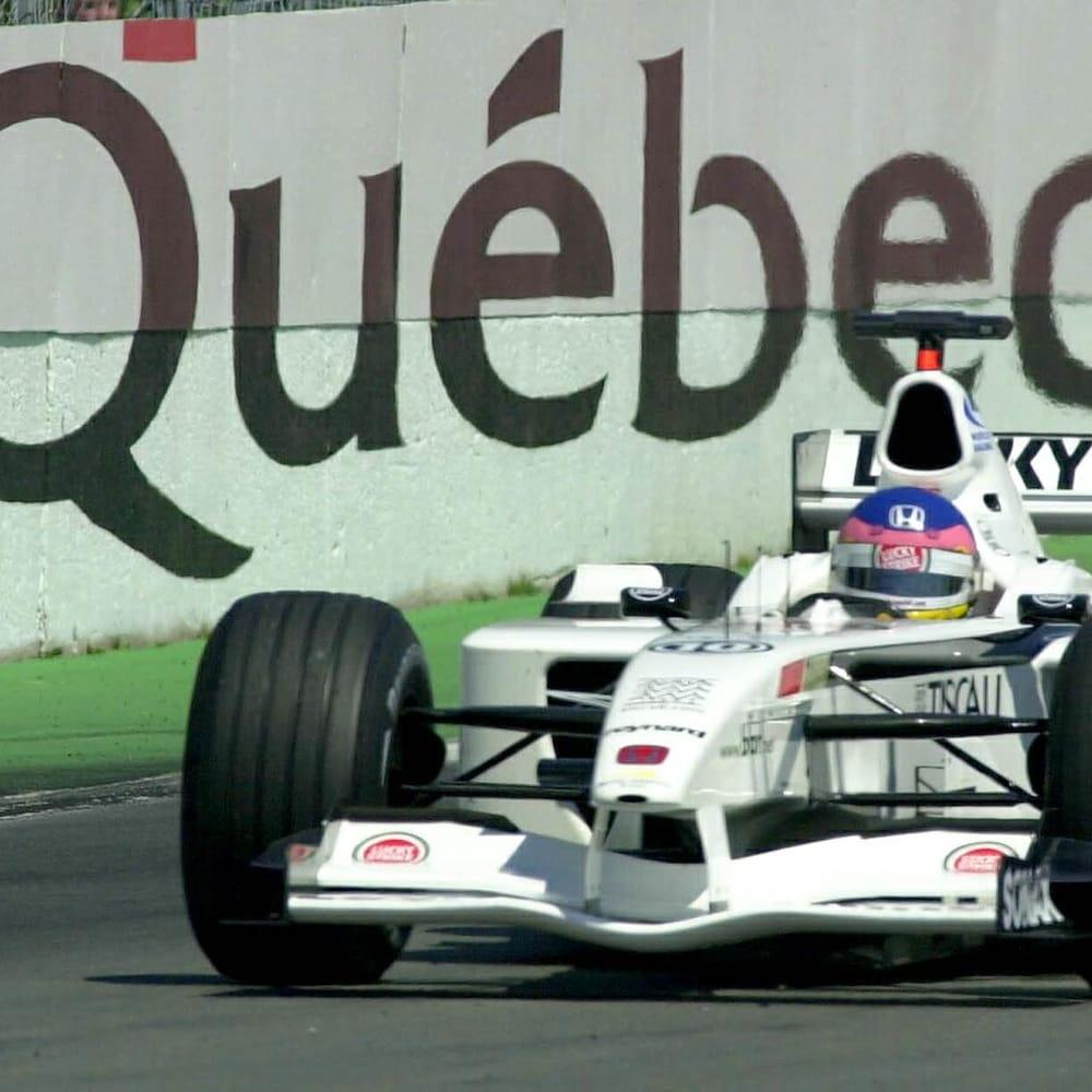 """Une publicité gouvernementale peinte sur un mur dit : """"Bonjour Québec"""" alors que la voiture de Jacques Villeneuve passe devant."""