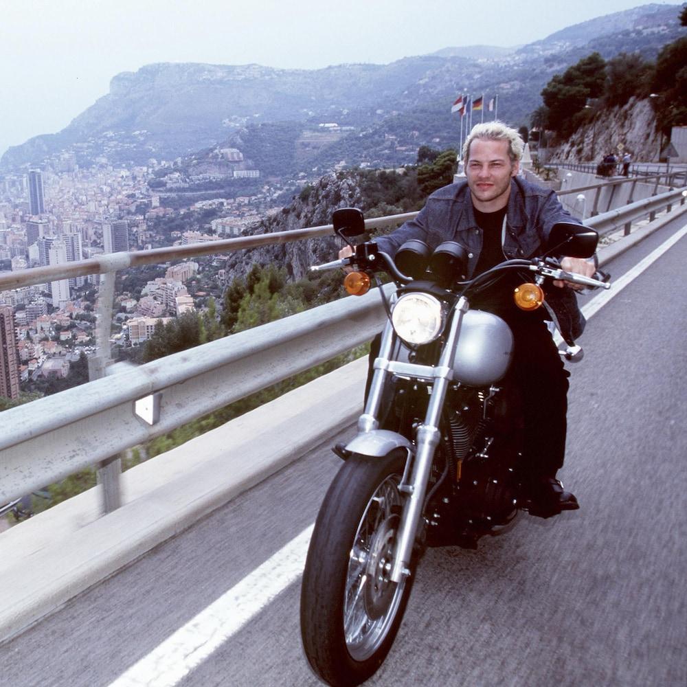 Jacques Villeneuve en moto sur une route surplombant la mer.