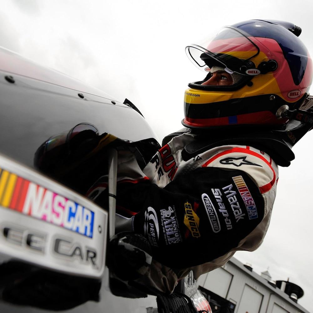 Jacques Villeneuve entre dans une voiture.