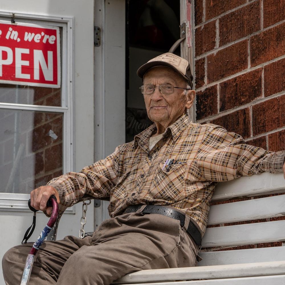 Boyd Stevens tenant sa canne, assis sur un banc à côté d'une porte portant un écriteau ''open'' d'un bâtiment délabré.