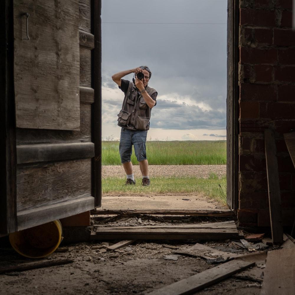 Johnnie Bachusky en train de photographier l'intérieur d'un vieux bâtiment.