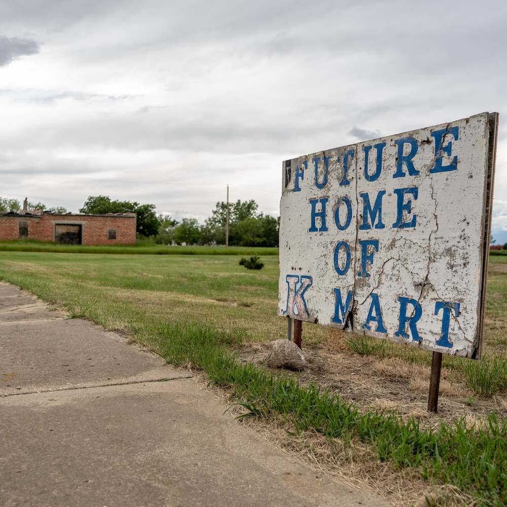 """Panneau en bois vieilli indique sur un terrain en friche """"Future home of KMart""""."""
