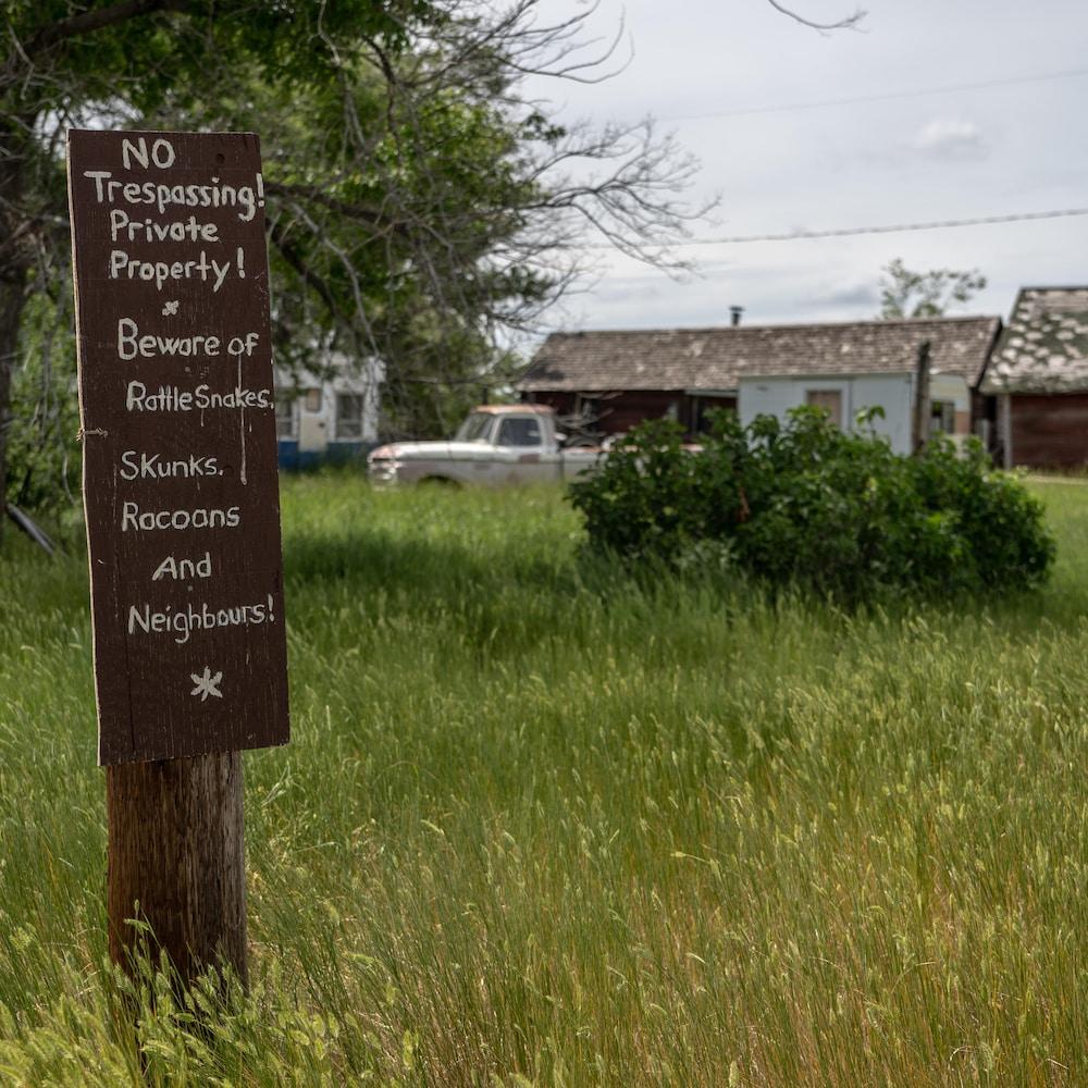Écriteau dans une cour près de vieux bâtiments : No Trespassing! Private Property. Beware of rattlesnakese, skunks, racoons and neighbours!
