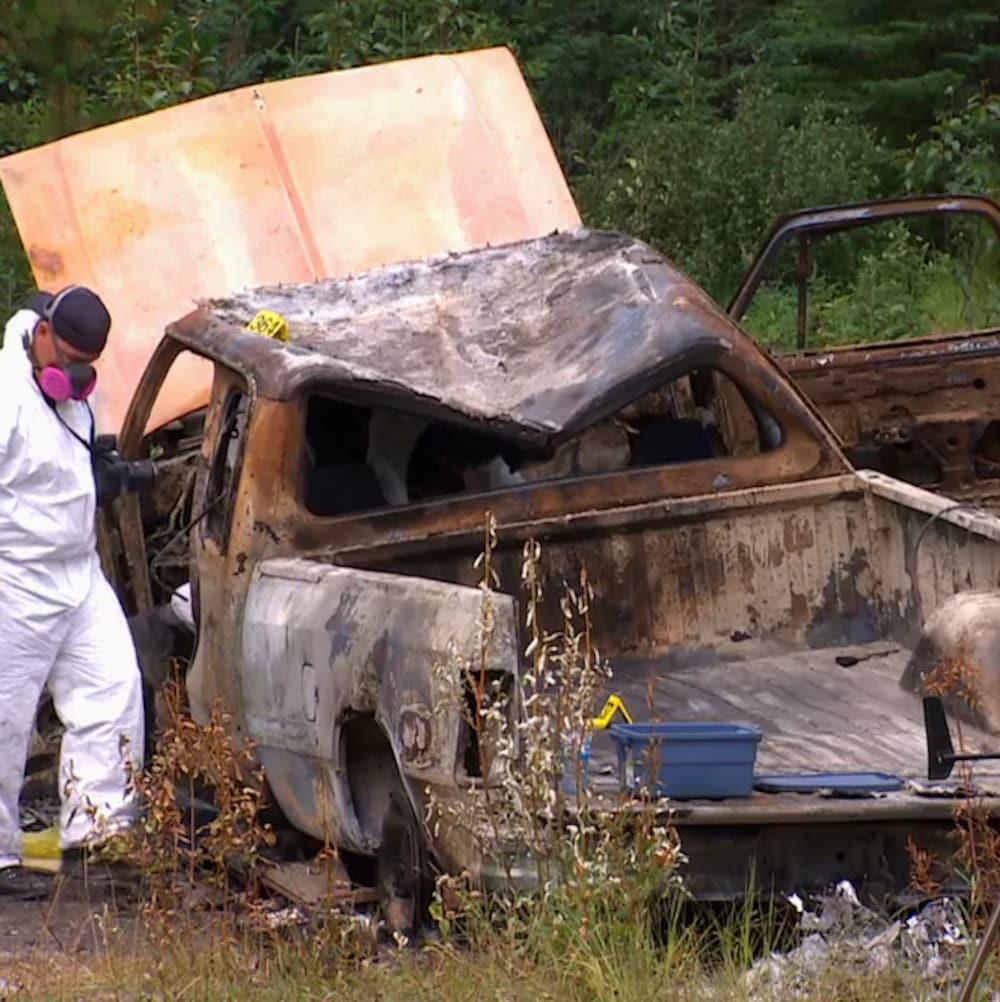 Une voiture brûlée avec un homme en combinaison blanche à côté.