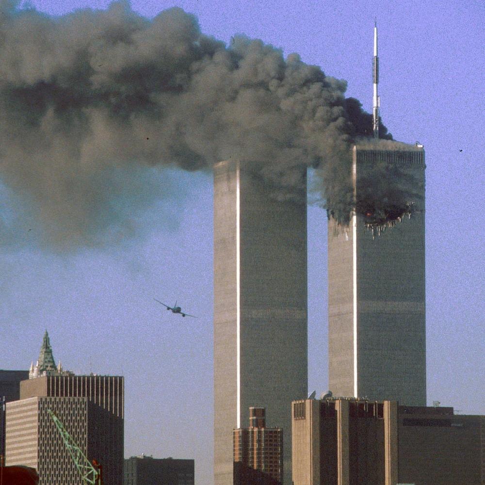 On voit les deux tours du World Trade Center, celle de droite est la proie d'une incendie et on y voit le trou béant résultant de l'impact du premier avion. À gauche, un appareil en vol se dirige sur la tour Sud.