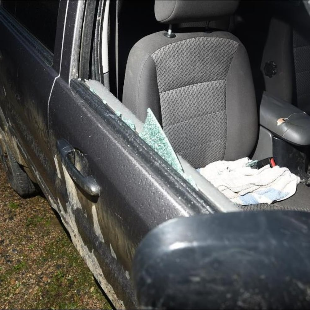 La vitre cassée du côté passager d'un VUS gris