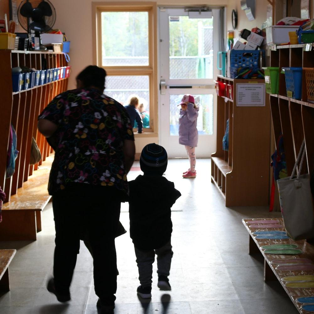 Une éducatrice et un enfant dans le couloir d'une garderie.