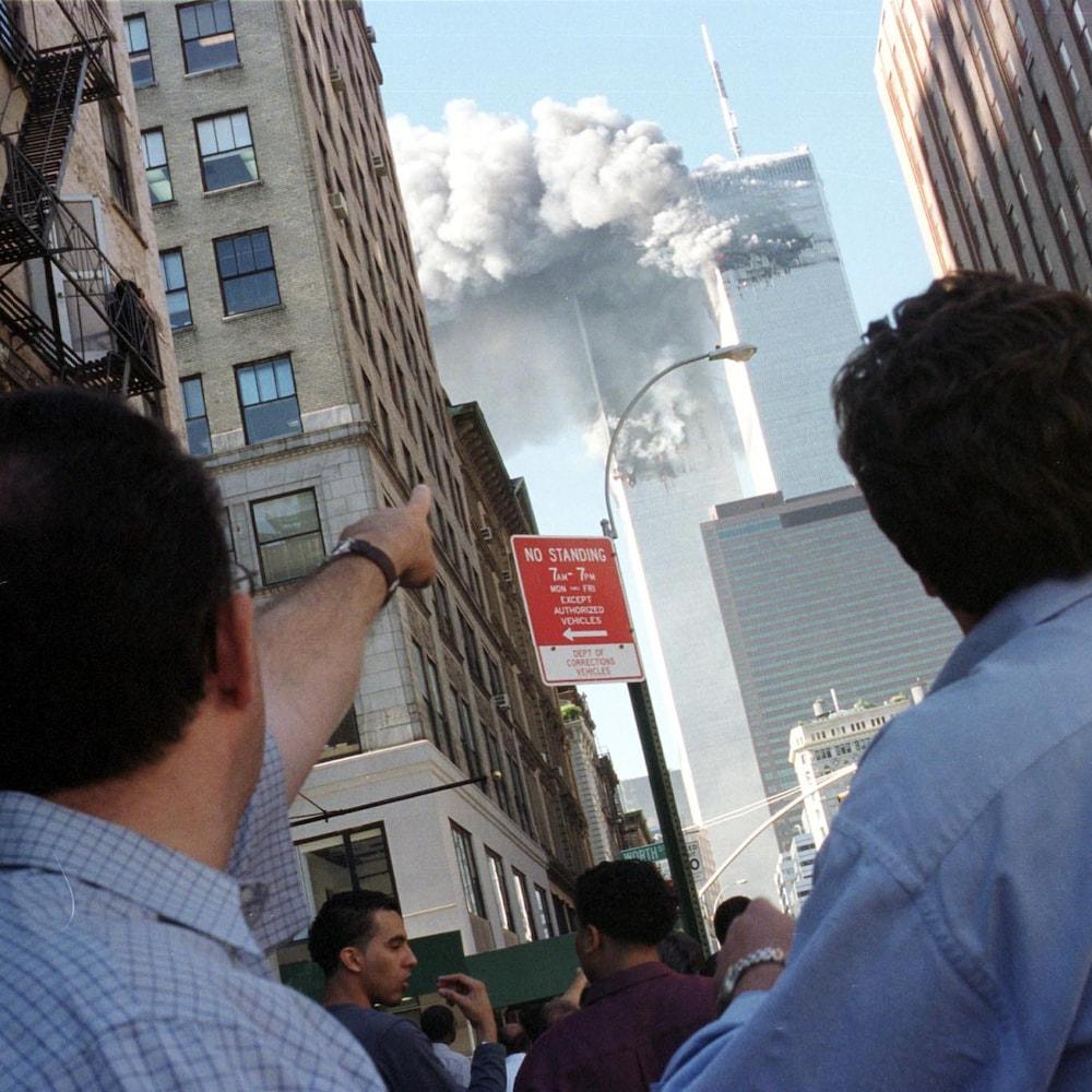 On voit au premier plan, de dos, deux hommes qui observent les tours du World Trade Center enfumées, en contre-plongée. Celui de gauche pointe l'édifice. La tour de gauche commence à s'effondrer.