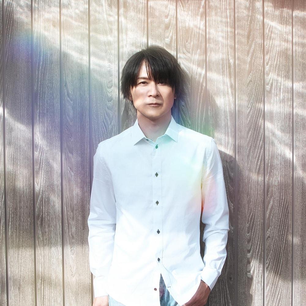 Yasunori Mitsuda est un homme dans la trentaine qui pose pour la caméra. Il porte une chemise blanche et ses longs cheveux foncés tombent au-dessus de ses yeux.