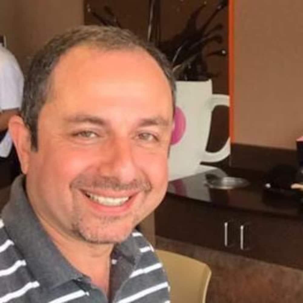 M. Mouzahem souriant en prenant un égoportrait.