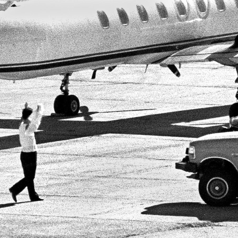Un membre de l'équipage de la Korean Air se dirige vers un camion de l'équipe d'intervention d'urgence de la GRC avec sa chemise et les mains en l'air à l'aéroport international de Whitehorse.