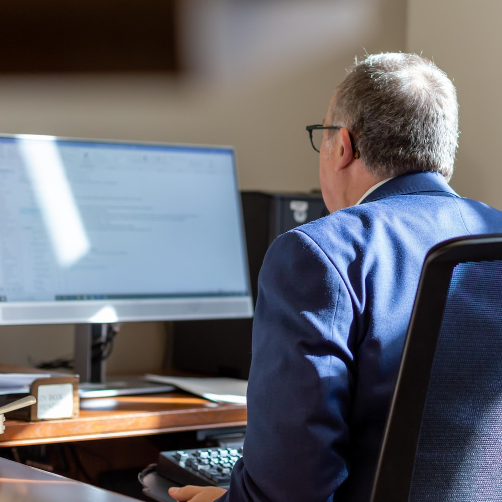 Yves Perron devant son ordinateur avec son lunch à côté de lui.