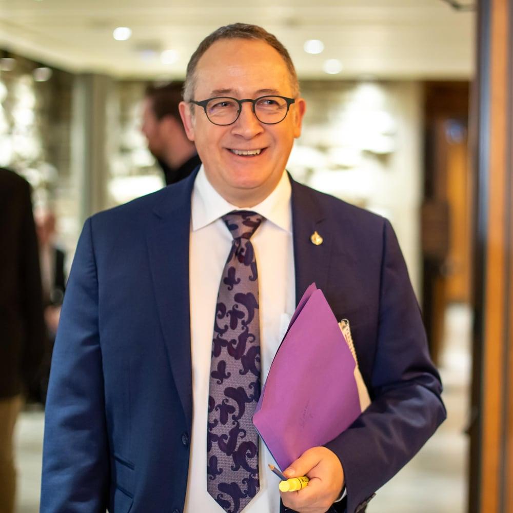 Yves Perron dans le couloir du parlement temporaire, avec un dossier dans les mains.