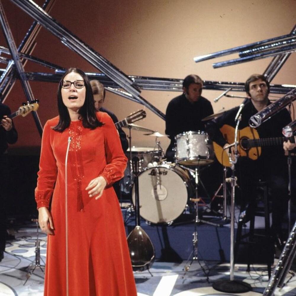 Nana Mouskouri sur scène entourée de musiciens.