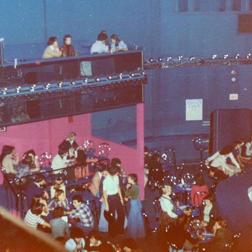 Des gens sont attablés dans la discothèque.