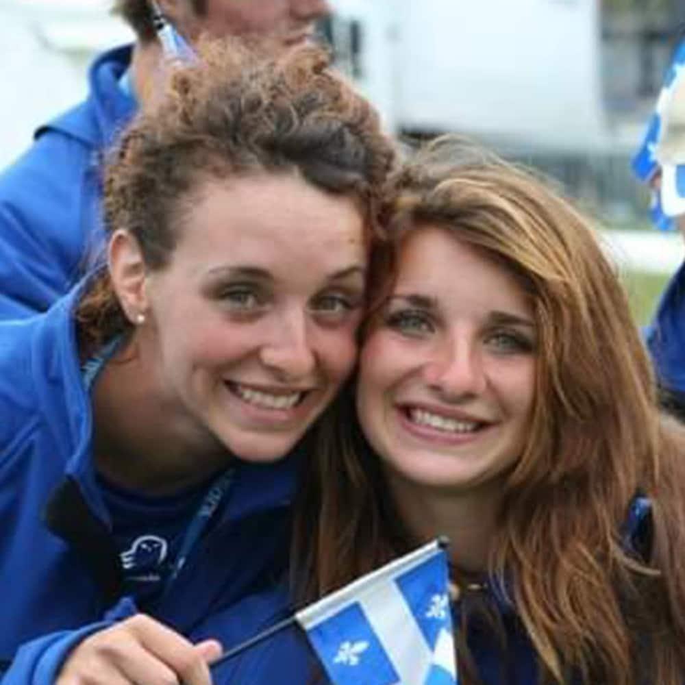 Deux femmes regardent la caméra et tiennent un drapeau du Québec.