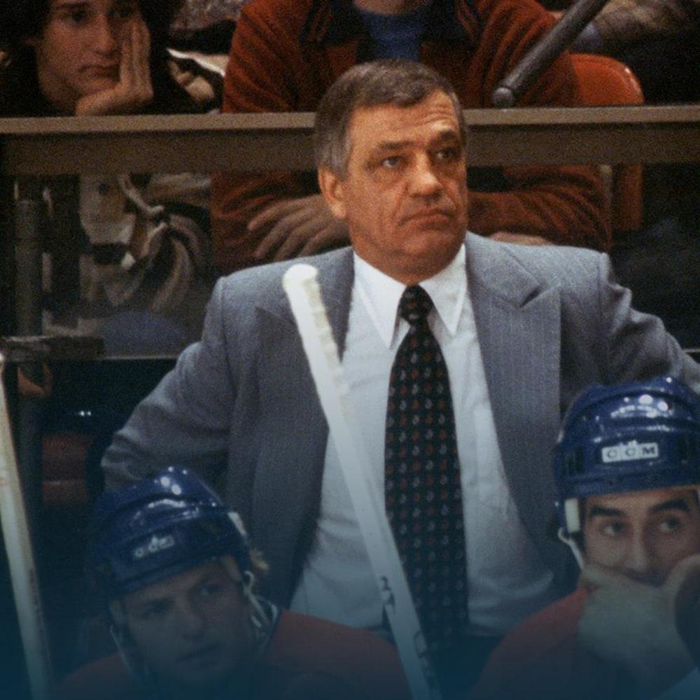 Posté derrière le banc du Canadien de Montréal, Bernard Geoffrion regarde l'action qui se déroule sur la patinoire.