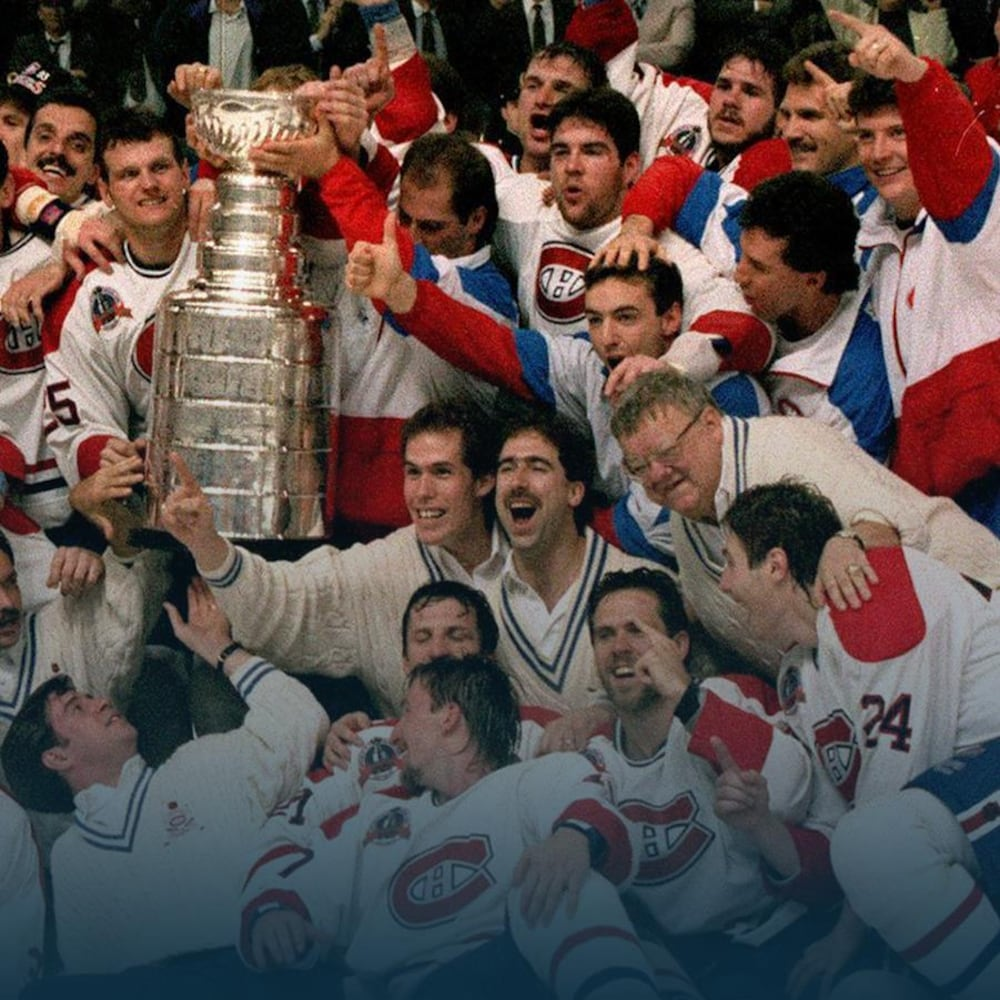 Un groupe de joueurs de hockey sourient et entourent la coupe Stanley.