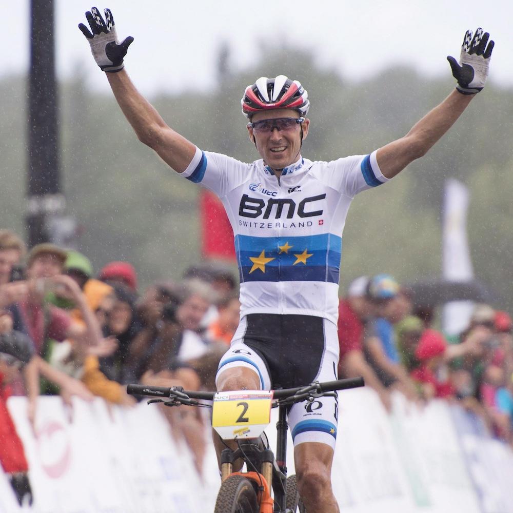 Le Français Julien Absalon lève les bras pour célébrer sa victoire à la Coupe du monde de vélo de montagne de mont Sainte-Anne, en 2016.