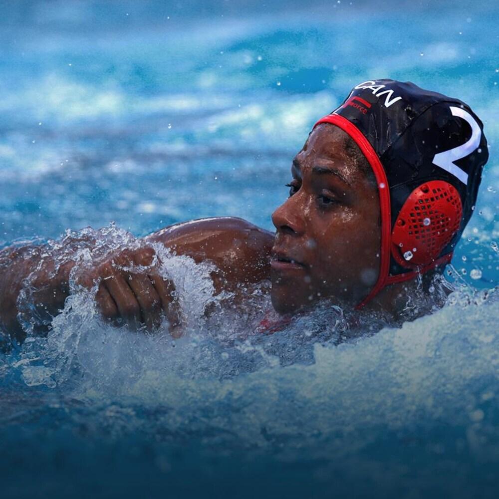 Une joueuse de water-polo regarde flotter un ballon.