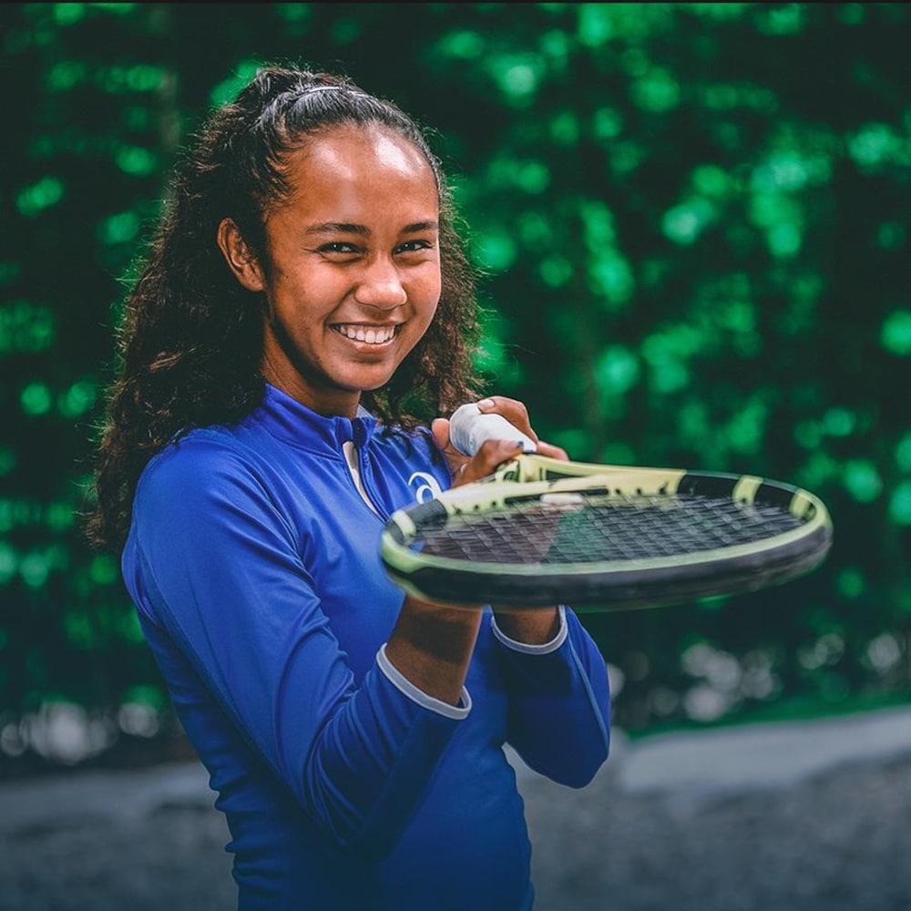 Leylah Annie Fernandez pointe la caméra avec sa raquette de tennis, en souriant.