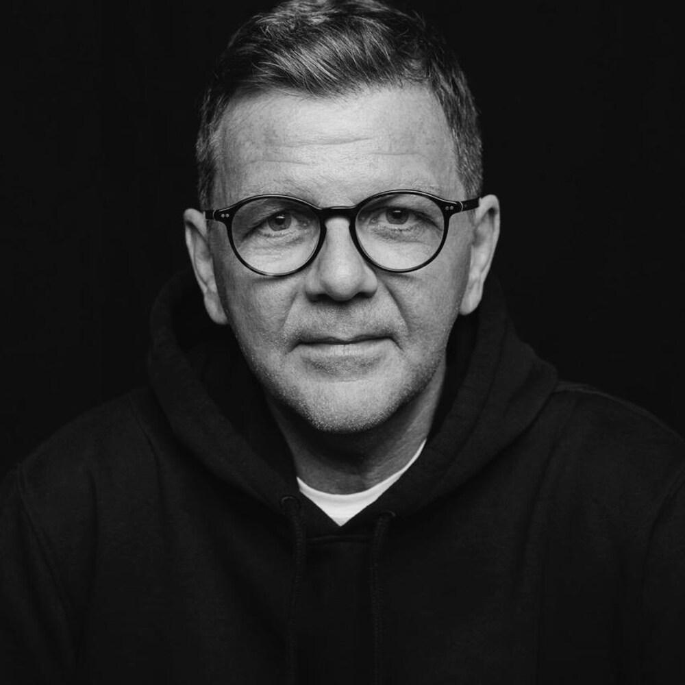 Photo en noir et blanc d'un homme portant des lunettes.