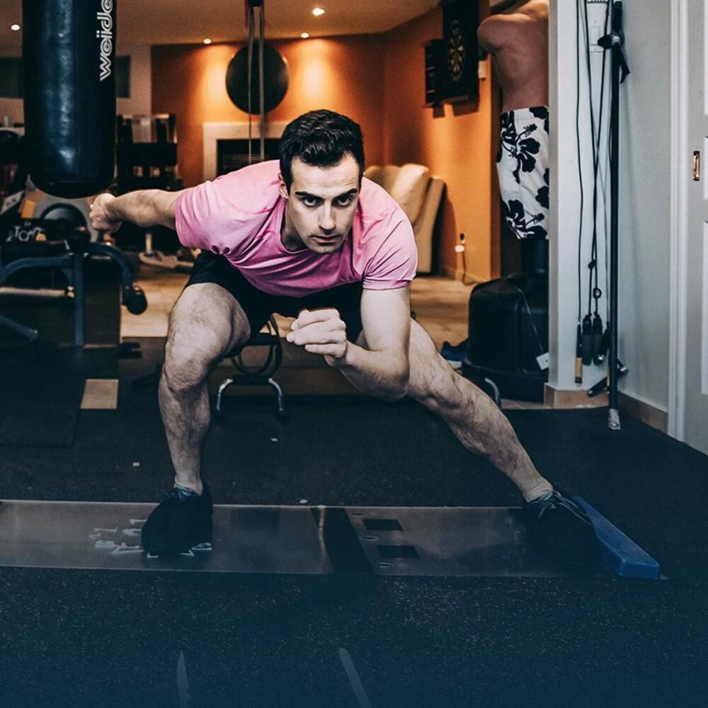 Le patineur de vitesse glisse latéralement en faisant un exercice à l'entraînement dans sa maison.