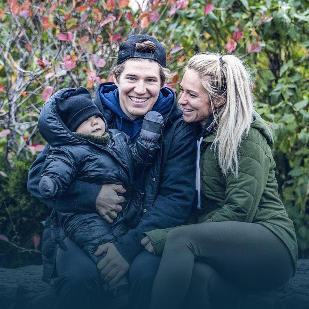 Maxime et Marylou sourient en tenant leur fils dans leurs bras.