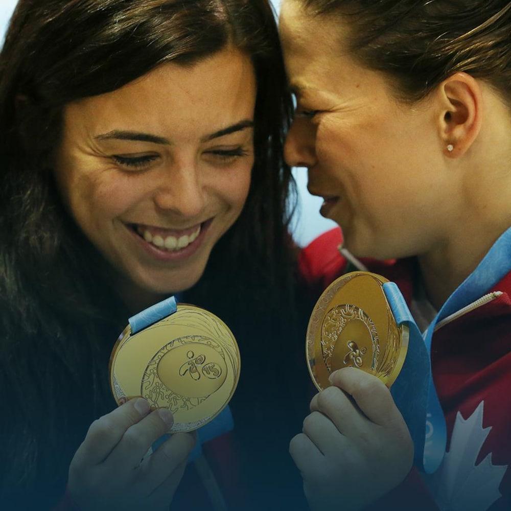Deux jeunes femmes s'étreignent en montrant leurs médailles d'or.