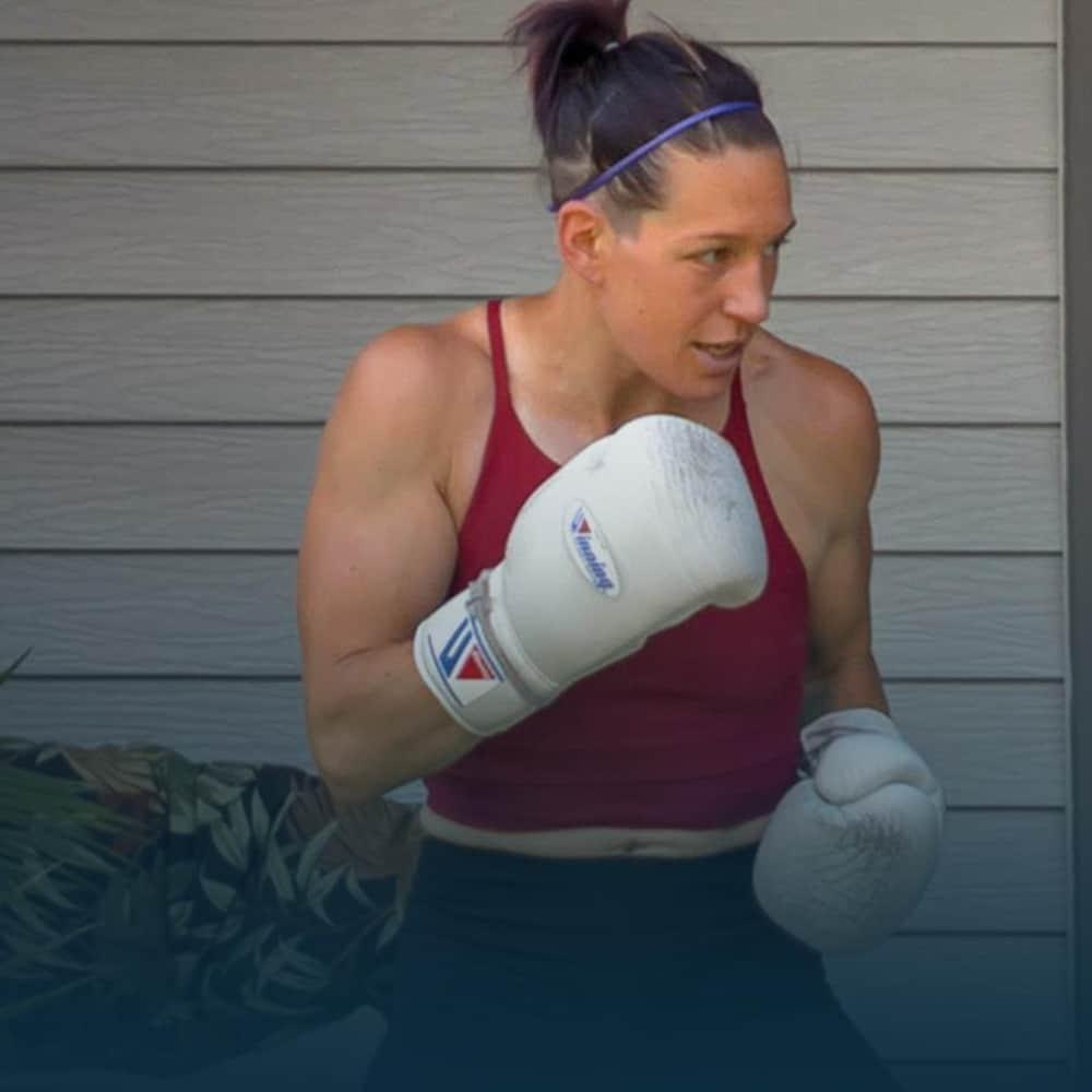 Une boxeuse s'entraîne en frappant sur un sac dans sa cour arrière.