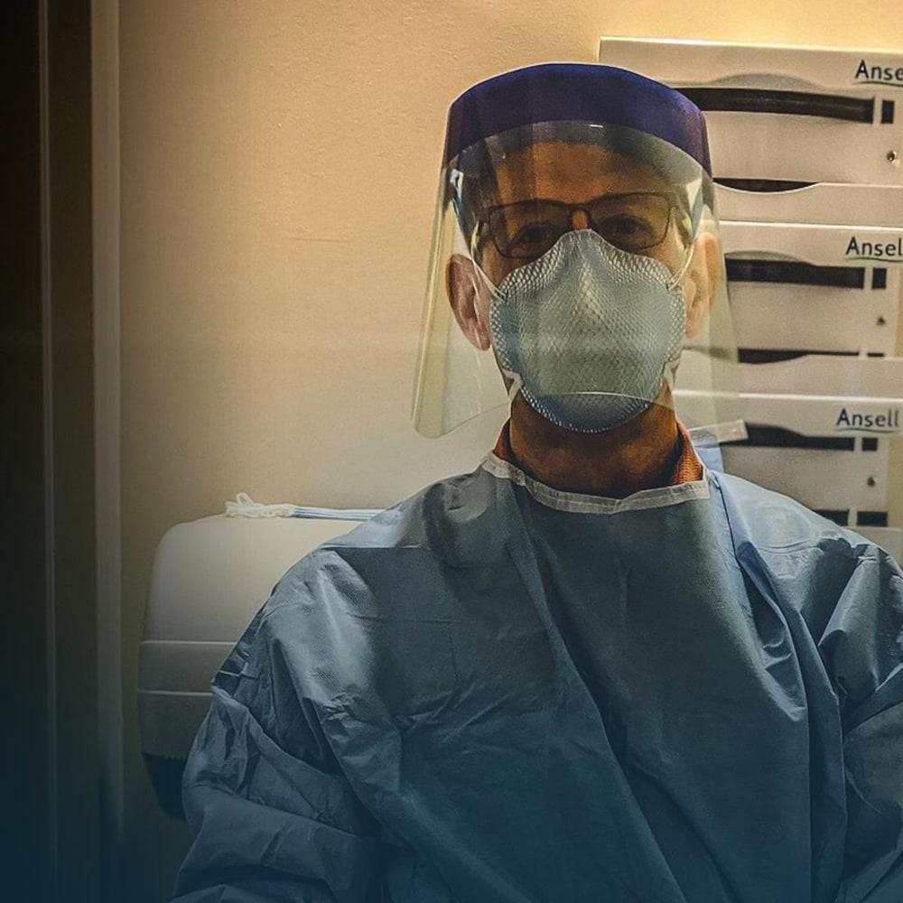 Sébastien Roulier, portant une visière et un masque médicaux, regarde la caméra.