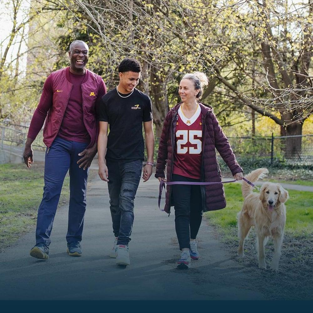 Un homme, une femme et leur fils adolescent marchent dans un parc en souriant.