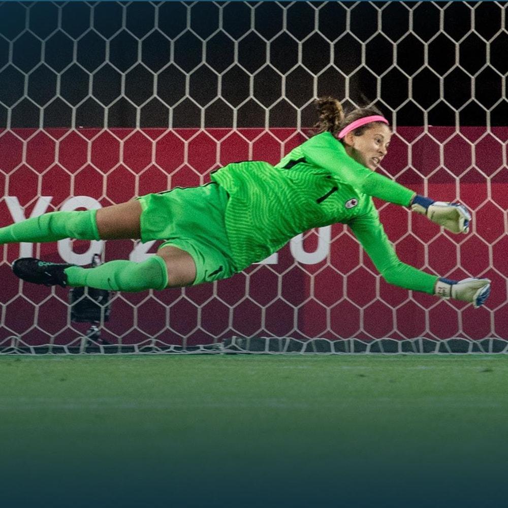 Une gardienne de but au soccer se jette dans les airs pour arrêter un ballon.