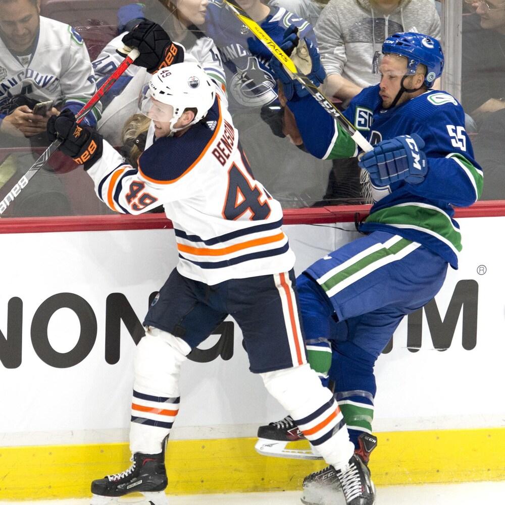 Tyler Benson bataille avec Alex Biega des Canucks pour l'obtention de la rondelle.