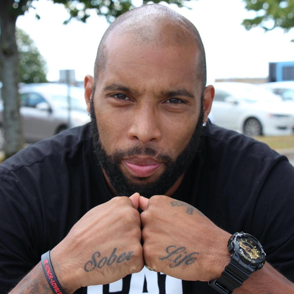 Portrait d'Éric, qui regarde la caméra d'un air sérieux. Il montre un tattoo sur ses deux mains qui, une fois jointes ensemble, forment les mots «Sober Life».