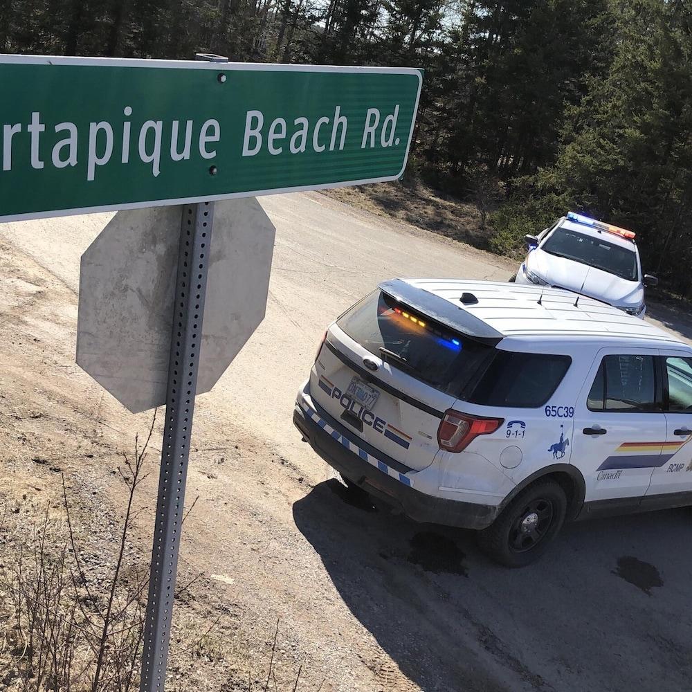 Panneau routier de la route Portapique Beach et deux véhicules de police qui bloquent l'entrée de la route.