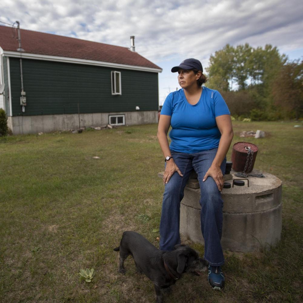 La policière Lisa Commanda, ici assise sur son puits, a construit sa maison à Kitigan Zibi en 2001. Elle n'a jamais bu de l'eau du robinet.