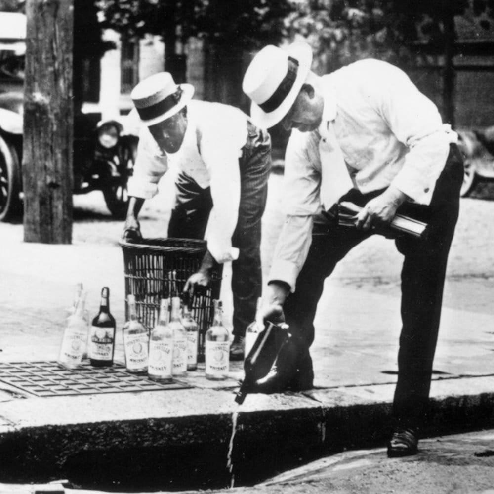 Des hommes dans la rue vident le contenu de bouteilles d'alcool.