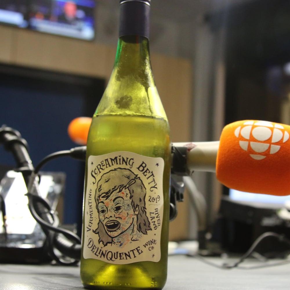 Photo d'une bouteille de vin blanc avec une étiquette qui représente une femme tatouée au visage.