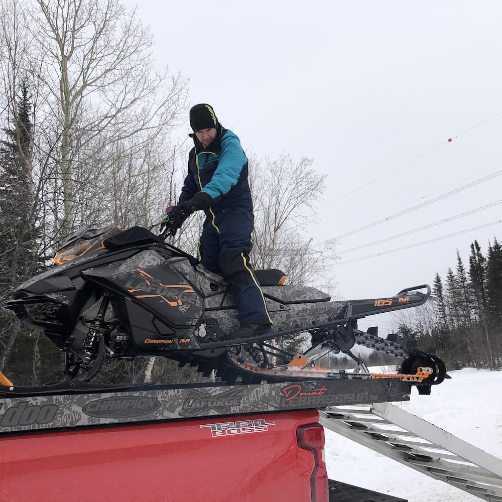 Donat Lebrasseur qui descend sa motoneige de la boîte de son camion