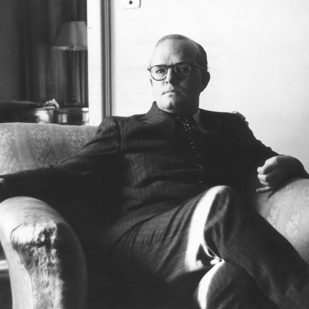 Truman Capote assis dans un fauteuil.