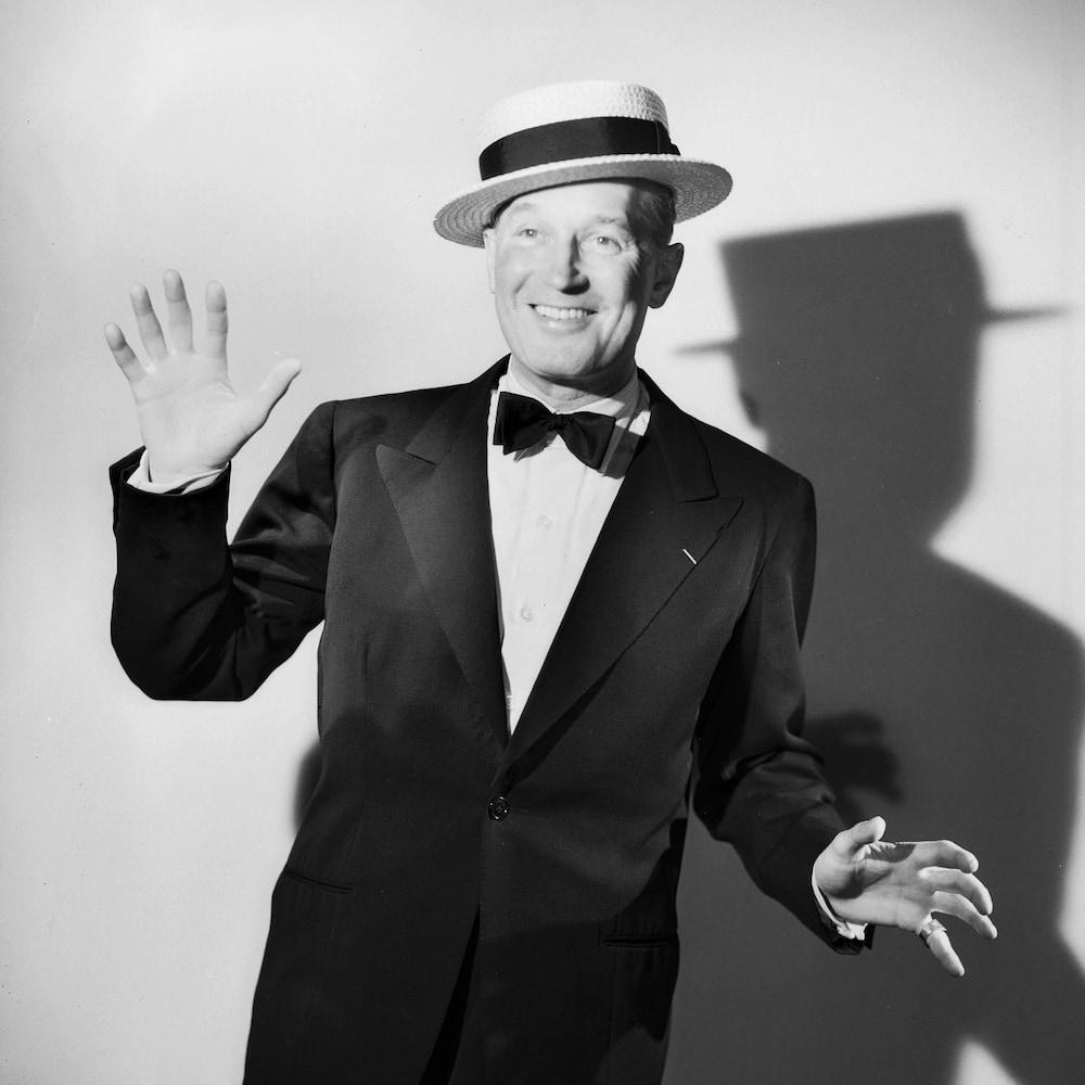 Maurice Chevalier fait quelques pas de danse devant un fond blanc.