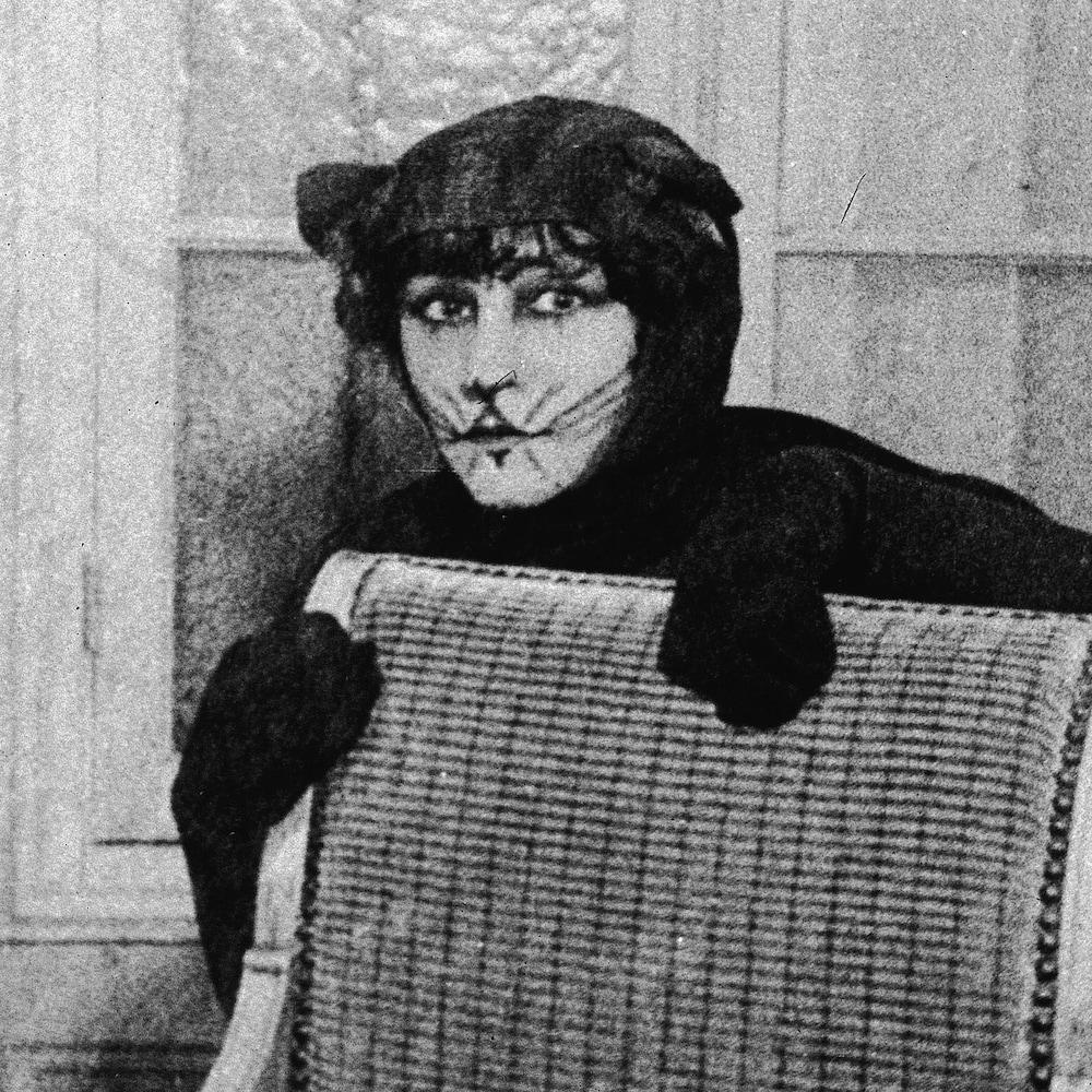 Colette, costumée en chat, se cache derrière une chaise dans cette photo datant de 1912.