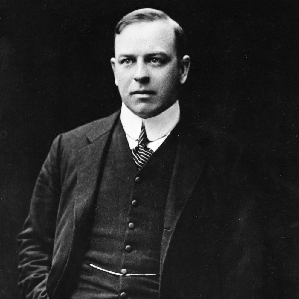 Mackenzie King debout, regardant à sa droite, la main dans la poche.